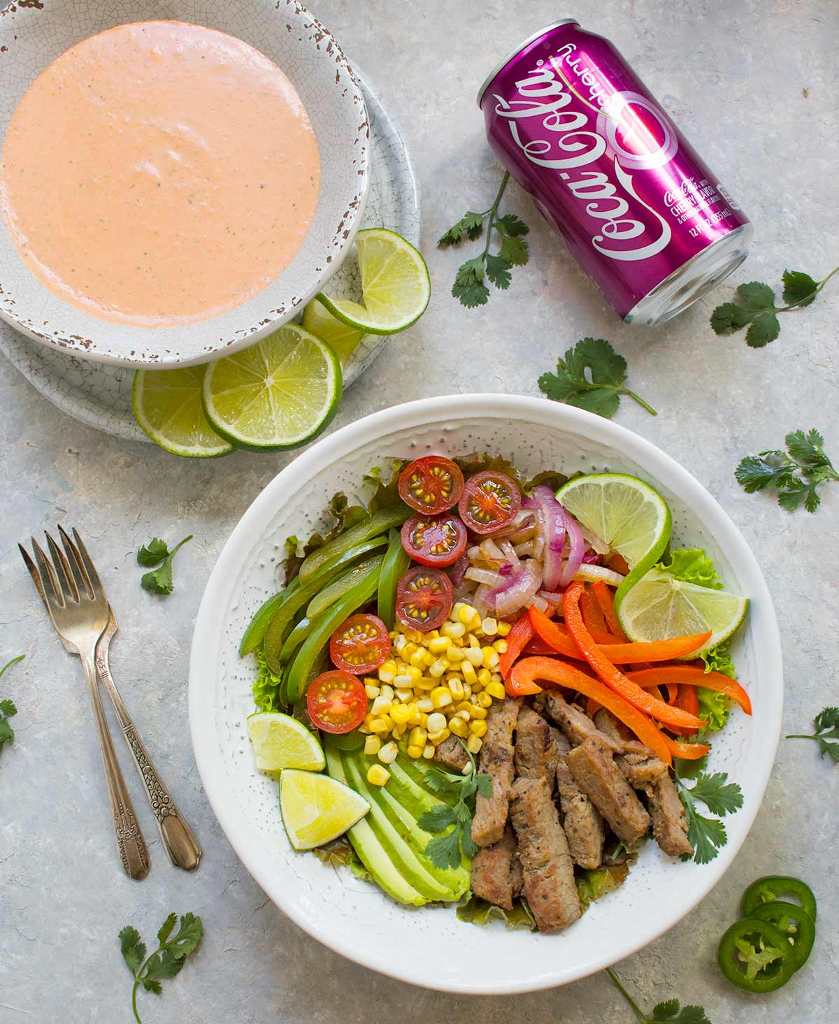 Beef Fajita Salad with Creamy Salsa Dressing, served in a bowl, with a can of Cherry Coke. Recipe at SoupAddict.com